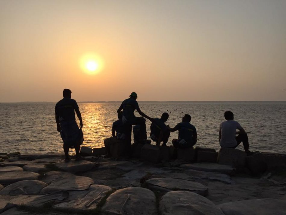 A group of friends sitting in front of river in Manpura Island, Bangladesh and enjoying the wonderful sunset
