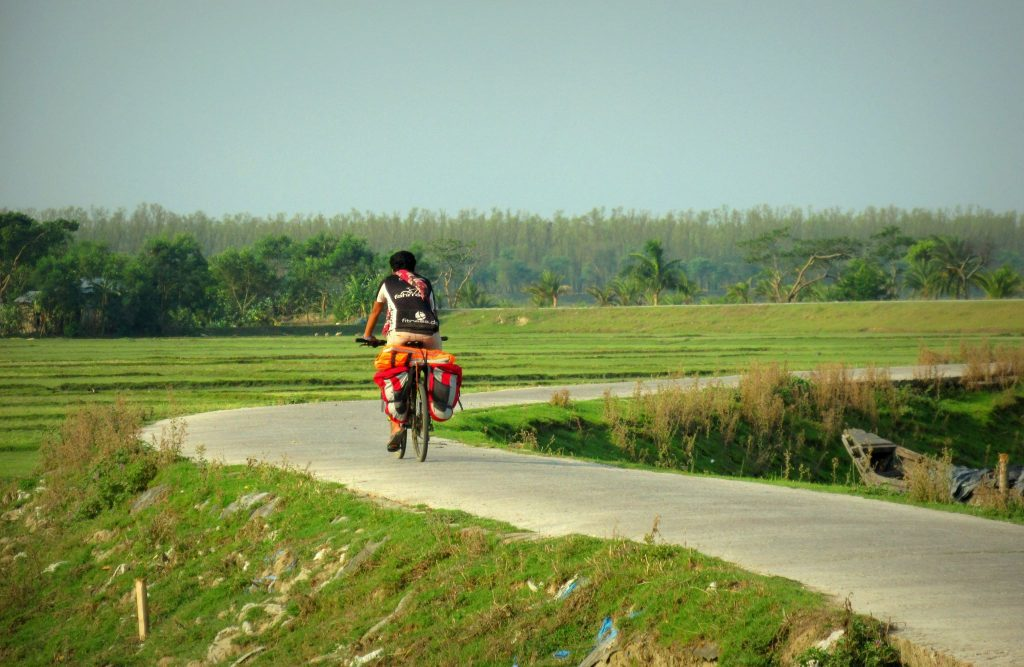 A villager riding on a cycle in beautiful road of Manpura Island, Bangladesh