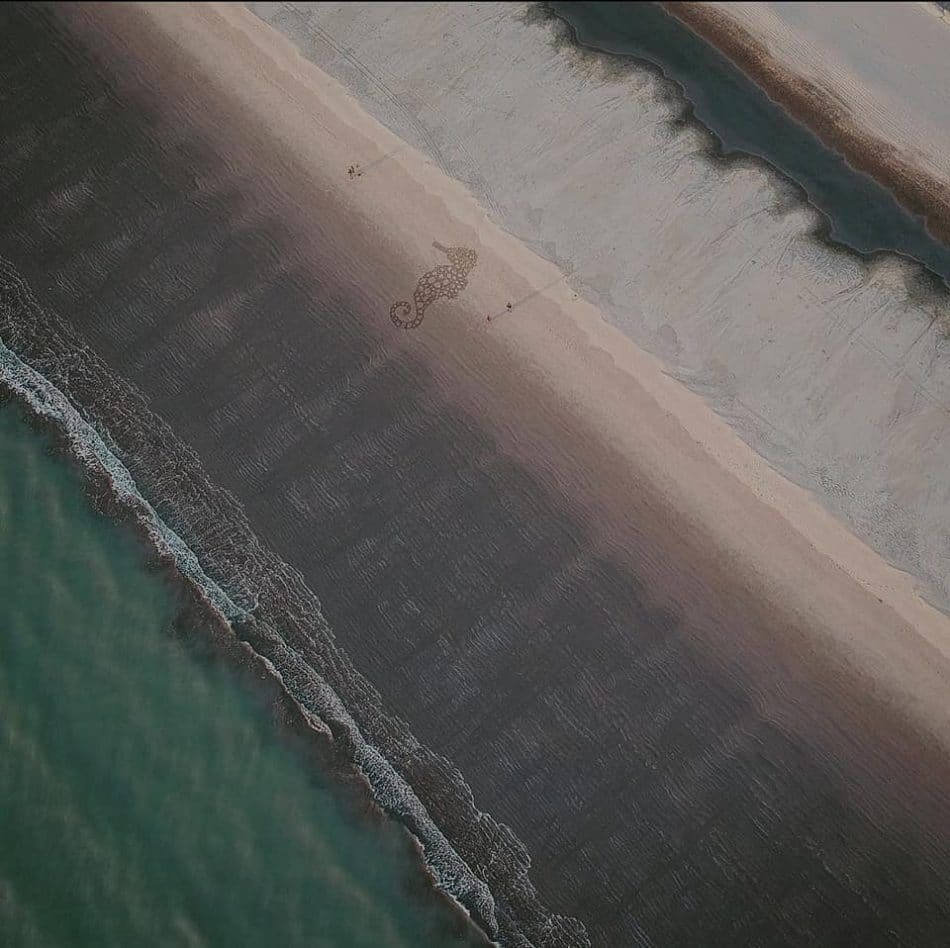 Drone view of Cox's Bazar sea beach in bangladesh. Two-person and sea horse drawing on the beach sand.
