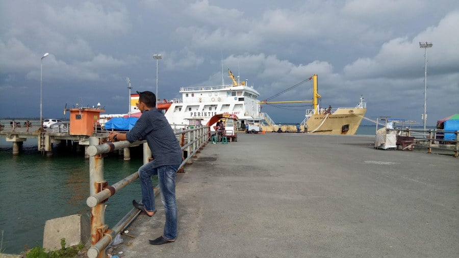 Lanaga Meulaboh Beach, Aceh - A man standing in bridge and ship is on the water